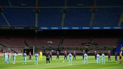 Para pemain Barcelona dan Leganes mengheningkan cipta sebelum bertanding pada pertandingan La Liga Spanyol di Camp Nou, Barcelona, Spanyol, Selasa (16/6/2020). Barcelona menang 2-0 lewat gol Ansu Fati dan Lionel Messi. (AP Photo/Joan Montfort)