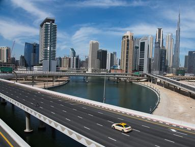 Sebuah taksi melintasi jalan raya yang sepi dekat Burj Khalifa di Dubai, Uni Emirat Arab, Senin (6/4/2020). Pemerintah Dubai memberlakukan lockdown selama dua pekan untuk mengantisipasi penyebaran virus corona COVID-19. (AP Photo/Jon Gambrell)