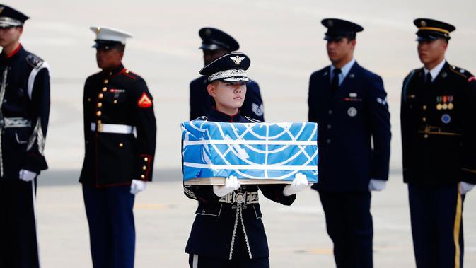 Pasukan PBB membawa kotak berisi jenazah yang diyakini sebagai tentara Amerika Serikat (AS) yang tewas selama Perang Korea pada tahun 1950-1953 di Pangkalan Udara Osan, Pyeongtaek, Korea Selatan, Jumat (27/7). (Kim Hong-Ji/Pool Photo via AP)