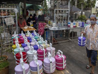 Sukarelawan menempatkan kotak-kotak berisi makanan di Masjid Bang Aw, Bangkok, Thailand, Kamis (30/4/2020). Setiap hari selama Ramadan, sukarelawan membagikan makanan kepada 150 keluarga sekitar Masjid Bang Aw yang tidak bisa beribadah bersama karena pandemi COVID-19. (AP Photo/Gemunu Amarasinghe)