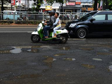 Pengendara mobil dan sepeda motor menghindari jalan yang ruas saat melintasi ruas Jalan Lapangan Ros, Tebet, Jakarta, Sabtu (11/5/2019). Jalan-jalan berlubang yang terisi air tersebut dapat mengakibatkan kecelakaan bagi pengendara kendaraan bermotor. (merdeka.com/Imam Buhori)