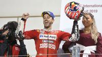Pembalap Ducati, Andrea Dovizioso berselebrasi usai berhasil memenangkan seri pembuka MotoGP di Sirkuit Internasional Losail di Doha, Qatar (10/3). Dovizioso berhasil mengalahkan Marc Marquez dengan selisih waktu 0,023 detik. (AP Photo/Hanson Joseph)
