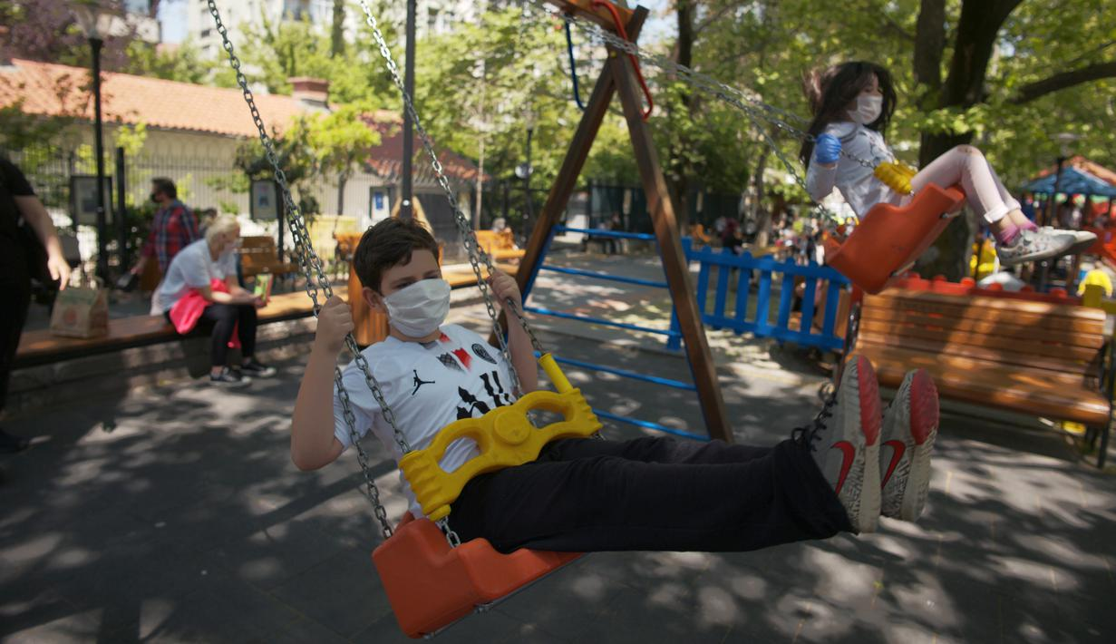 Anak-anak dengan mengenakan masker bermain ayunan di taman umum Kugulu, di Ankara, Rabu (13/5/2020). Turki mengizinkan anak-anak berusia 14 tahun ke bawah untuk meninggalkan rumah pertama kalinya dalam 40 hari sebagai bagian dari rencana normalisasi COVID-19 di negara tersebut. (AP/Burhan Ozbilici)