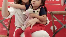 Keakraban selebritas Gisella Anastasia bersama sang anak Gempita Nora Marten saat menghadiri pembukaan stan produk minuman di Jakarta, Jumat (23/3). Gisel mengaku bahwa Gempi menyaingi ketenarannya sebagai pesohor hiburan. (Liputan6.com/Faizal Fanani)