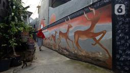 Warga berjalan dekat mural yang menghiasi tembok rumah warga RT 02/RW 07 Kampung Warna-warni, Kelurahan Pengadegan, Jakarta Selatan, Selasa (10/12/2019). Mural tersebut sebagai bentuk kesadaran warga untuk menciptakan kampung yang enak dipandang, bersih, aman, dan nyaman. (merdeka.com/Imam Buhori)