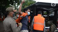 Warga yang terjaring razia protokol kesehatan COVID-19 mengenakan rompi di Kebon Nanas, Jakarta, Selasa (15/6/2021). Saat kasus positif Covid-19 di Jakarta meningkat, masih banyak warga yang belum menjalankan protokol kesehatan, salah satunya mengenakan masker. (merdeka.com/Imam Buhori)