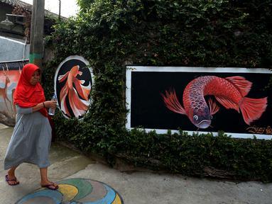 Warga berjalan dekat mural yang menghiasi tembok rumah warga RT 02/RW 07 Kampung Warna-warni, Kelurahan Pengadegan, Jakarta Selatan, Selasa (10/12/2019). Mural di kampung ini dibuat dari dana swadaya warga setempat. (merdeka.com/Imam Buhori)