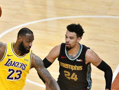 Pebasket Los Angeles Lakers, LeBron James, berusaha melewati pebasket Memphis Grizzlies, Dillon Brooks, pada laga NBA, Rabu (6/1/2021). LA Lakers menang tipis 94-92 atas Grizzlies. (AP Photo/Brandon Dill)