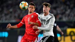 Gelandang Jerman, Kai Havertz, duel udara dengan gelandang Serbia, Nemanja Maksimovic, pada laga persahabatan di Stadion Volkswagen, Rabu, (20/3). Jerman ditahan imbang 1-1 oleh Serbia. (AFP/Tobias Schwarz)