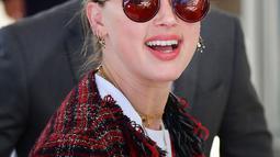 Aktris AS Amber Heard saat tiba untuk menghadiri malam pembukaan Festival Film Cannes ke-72 di Prancis (13/5/2019). Aktris 33 tahun ini mengenakan kaca mata merah, perhiasan emas, dan membawa tas rantai-tali YSL. (AFP Photo/Alberto Pizzoli)