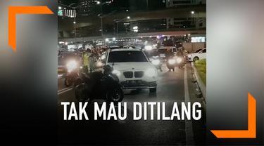 Sebuah mobil mewah tolak ditilang oleh petugas, pengemudi bahkan mencoba menabrak dan melarikan diri.
