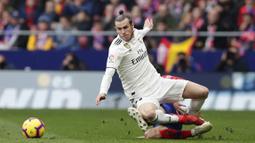 Penyerang Real Madrid, Gareth Bale, terjatuh saat berebut bola dengan pemain Atletico Madrid, Santiago Arias, pada laga La Liga di Stadion Wanda Metropolitano, Sabtu (9/2). Real Madrid menang 3-1 atas Atletico Madrid. (AP/Manu Fernandez)