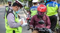 Polisi Lalu lintas menilang pengendara sepeda motor saat Operasi Patuh Jaya 2020 di Jalan Letjen Suprapto, Jakarta Pusat, Kamis (23/7/2020). Ditlantas Polda Metro Jaya menggelar Operasi Patuh Jaya 2020 hingga 5 Agustus untuk menertibkan masyarakat dalam berlalu lintas. (Liputan6.com/Faizal Fanani)