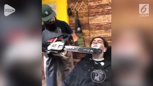 Aksi berbahaya dilakukan tukang cukur yang menggunakan gergaji mesin sebagai alat cukur.