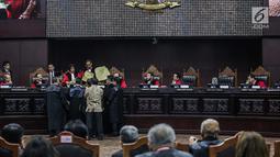 Majelis Hakim mengecek amplop yang dibawa Komisioner KPU, Hasyim Asyari selama sidang sengketa pilpres 2019 di Gedung MK, Jakarta, Kamis (20/6/2019). Kode tertentu menunjukkan bahwa amplop tersebut untuk menyimpan salinan form C1. (Liputan6.com/Faizal Fanani)