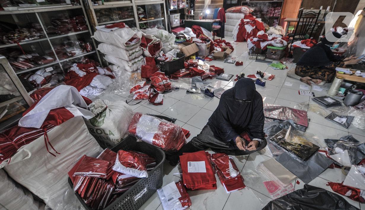 Pekerja mengemas bendera Merah Putih untuk dikirim melalui jasa kurir di industri rumahan benderaindonesia.com, Jakarta, Selasa (3/8/2021). Menjelang Hari Kemerdekaan RI penjualan bendera Merah Putih dan pernak pernik 17 Agustus-an via online meningkat hingga 50 persen. (merdeka.com/Iqbal S Nugroho)