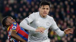 Striker Manchester United, Alexis Sanchez melewati pemain Crystal Palace Aaron Wan-Bissaka saat pertandingan Liga Inggris di Selhurst Park, London (5/3). Pada pertandingan ini MU sempat tertinggal 0-2 atas Crystal Palace. (AP Photo/Tim Ireland)