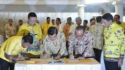 Wapres Jusuf Kalla (tengah) bersama Ketum Partai Golkar versi munas Bali Aburizal Bakrie dan Ketum Partai Golkar versi munas Ancol Agung Laksono (kedua kiri) saat penandatangan berkas kesepakatan islah di Jakarta, Sabtu (30/5). (Liputan6.com/Johan Tallo)