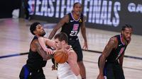 Pebasket Denver Nuggets, Nikola Jokic , berebut bola dengan pebasket Los Angeles Clippers,Paul George, pada gim ketujuh semifinal playoff NBA di Lake Buena Vista, Selasa (15/9/2020).  Nuggets menang dengan skor 104-89. (AP/Mark J. Terrill)