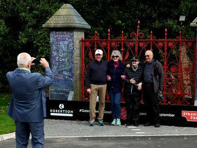 "Pengunjung berpose di depan gerbang  Strawberry Fields yang baru dibuka untuk umum di Liverpool, Rabu (18/9/2019). Strawberry Field menjadi salah satu tempat ikonis ketika John Lennon menulis lagu The Beatles ""Strawberry Fields Forever"" dalam album Sgt.pepper Lonely Hearts Club Band (Paul ELLIS/AFP)"