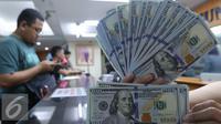 Petugas menunjukkan mata uang Dolar Amerika di toko penukaran uang di Jakarta, Selasa (7/6). Dolar AS kembali melemah terhadap rupiah. Mata uang Paman Sam ini bergerak dikisaran Rp 13.300. (Liputan6.com/Angga Yuniar)