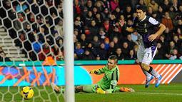 Luis Suarez (kanan) mencetak gol kedua untuk Liverpool, melewati kiper Stoke City Jack Butland saat pertandingan sepak bola Liga Utama Inggris antara Stoke City melawan Liverpool di The Britannia stadion, pada (12/01/14) waktu setempat.(Foto: AFP/Andrew Y