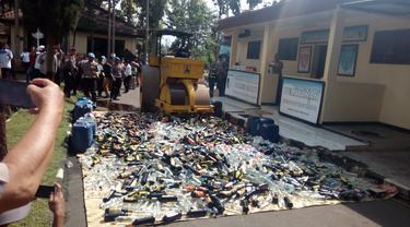 Nampak alat berat tengah memusnahkan ribuan botol miras hasil razia polres Garut