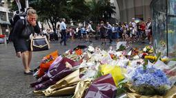 Seorang wanita bereaksi usai meletakkan bunga sebagai penghormatan bagi korban penyanderaan di Kafe Lindt, Sidney, Australia (16/12/2014). Tiga orang tewas dan empat terluka dalam penyanderaan yang terjadi selama lebih dari 16 jam. (REUTERS/Jason Reed)
