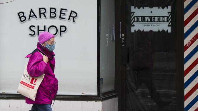Seorang wanita yang mengenakan masker berjalan melewati tempat pangkas rambut yang tutup di Toronto, Kanada, 23 November 2020. Kanada melaporkan 5.119 kasus baru COVID-19 dan tambahan 49 kematian pada 23 November 2020 malam waktu setempat. (Xinhua/Zou Zheng)