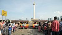Sejumlah warga antri untuk menaiki kereta wisata di halaman Monumen Nasional, Jakarta, Kamis (7/7). Libur kedua Lebaran dimanfaatkan warga untuk bekunjung ke lokasi wisata bersama keluarga. (Liputan6.com/Yoppy Renato)