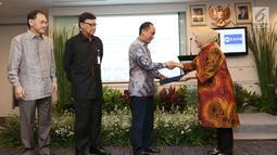 Dirjen Dukcapil, Zudan ArifFakrulloh (kedua kanan) disaksikan Komisaris Utama PT Emtek Eddy Sariaatmadja, Mendagri Tjahyo Kumolo bersalaman dengan Direktur PT. Emtek Yuslinda Nasution (kanan) di Jakarta, Jumat (13/7). (Liputan6.com/Angga Yuniar)