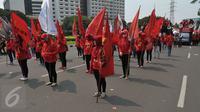 Sejumlah wanita membawa bendera saat aksi Hari Buruh di Jakarta, Senin (1/5). Dalam aksinya para buruh meminta sistem kerja kontrak dan upah rendah dihapus. (Liputan6.com/Helmi Afandi)