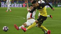 Gelandang Dortmund,  Jadon Sancho berusaha mengumpan bola dari kawalan bek PSG, Marquinhos pada pertandingan leg pertama babak 16 Liga Champions di Dortmund, Jerman (18/2/2020). Dortmund menang 2-0 atas PSG. (Bernd Thissen/dpa via AP)