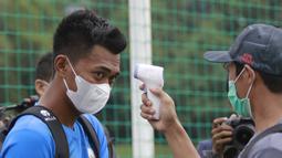 Pemain Timnas Indonesia dicek suhu tubuh sebelum sesi latihan di Lapangan D Senayan, Jakarta, Rabu, (10/2/2021). Latihan tersebut untuk persiapan SEA Games 2021 di Vietnam. (Bola.com/M Iqbal Ichsan)