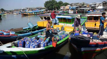 Nelayan memindahkan air bersih dengan jiriken untuk dibawa dalam perahu di Jakarta Utara, Rabu (9/5). Para nelayan tersebut harus membeli air bersih untuk kebutuhan mencari ikan. (Liputan6.com/Angga Yuniar)