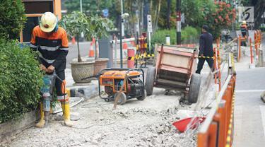 Pekerja membongkar jalur pejalan kaki (trotoar) di Jalan Cikini Raya, Jakarta, Jumat (14/6/2019). Pemprov DKI bakal melakukan revitalisasi  trotoar di Jalan Cikini Raya dan Jalan Kramat Raya sepanjang 10 kilometer dengan anggaran sebesar Rp75 miliar. (Liputan6.com/Immanuel Antonius)