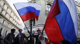 Suporter Rusia mengibarkan bendera menyambut gelaran Piala Dunia di Jalan Nikolskava, Moskow, Rabu (13/6/2018). Piala Dunia 2018 akan berlangsung pada 14 Juni hingga 15 Juli mendatang. (AP/Rebecca Blackwell)