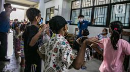 Anak-anak korban banjir bermain bersama relawan Forum Anak Jakarta Timur di tempat pengungsian di Gedung SD Kampung Melayu 01/02, Kebon Pala, Jakarta, Selasa (9/2/2021). Anak-anak diajak untuk bersenang-senang di tengah keterbatasan di pengungsian. (Liputan6.com/Faizal Fanani)