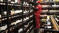 Seorang pria mengisi rak dengan botol anggur di toko minuman keras ketika Afrika Selatan mencabut larangan penjualan alkohol dan rokok di Johannesburg, Selasa (18/8/2020). Pembelian alkohol dan rokok dilarang ketika Afsel memberlakukan lockdown ketat pada 27 Maret 2020. (AP Photo/Denis Farrell)