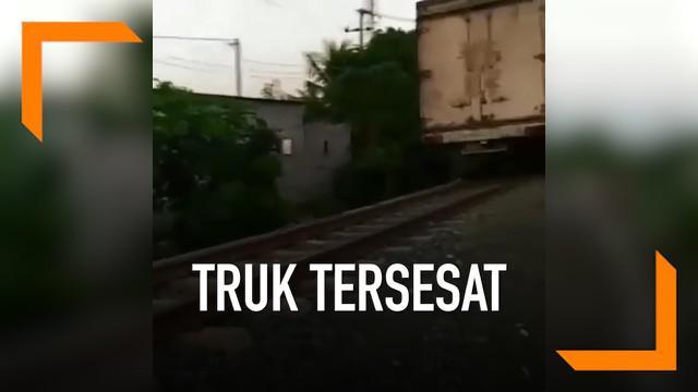 Sebuah truk tersesat hingga melaju di rel kereta api. Beruntung warga yang melihat meminta truk mundur agar tak terjadi tabrakan dengan kereta.