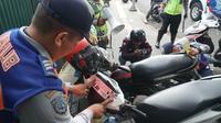 Petugas Dishub Kota Bandung menempelkan stiker sebagai sanksi kendaraan yang parkir sembarangan di Jalan Purnawarman, Jumat (14/6/2019). (Liputan6.com/Huyogo Simbolon)