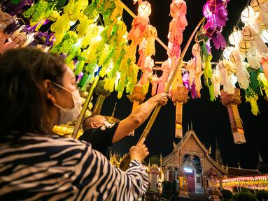 Orang-orang menggantung lampion di Wat Phra That Hariphunchai, Lamphun, Thailand, 1 November 2020. Sekitar 100.000 lampion digantung di Wat Phra That Hariphunchai sebagai bagian dari perayaan festival tradisional Yi Peng. (Xinhua/Zhang Keren)
