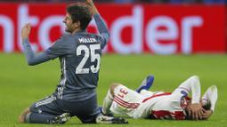 Bek Ajax Amsterdam, Nicolas Tagliafico, memegang kepala usai ditendang gelandang Bayern Munchen, Thomas Mueller, pada laga Liga Champions di Johan Cruyff Arena, Amsterdam, Rabu (12/12). Kedua tim bermain imbang 3-3. (AP/Peter Dejong)
