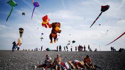 Orang-orang menerbangkan layang-layang selama Festival Layang-layang Internasional Dieppe ke-20 di Dieppe, Prancis, Minggu (9/9). Festival setiap dua tahun sekali sejak 1980 itu menjadi festival layang-layang terbesar di Eropa. (AFP/CHARLY TRIBALLEAU)