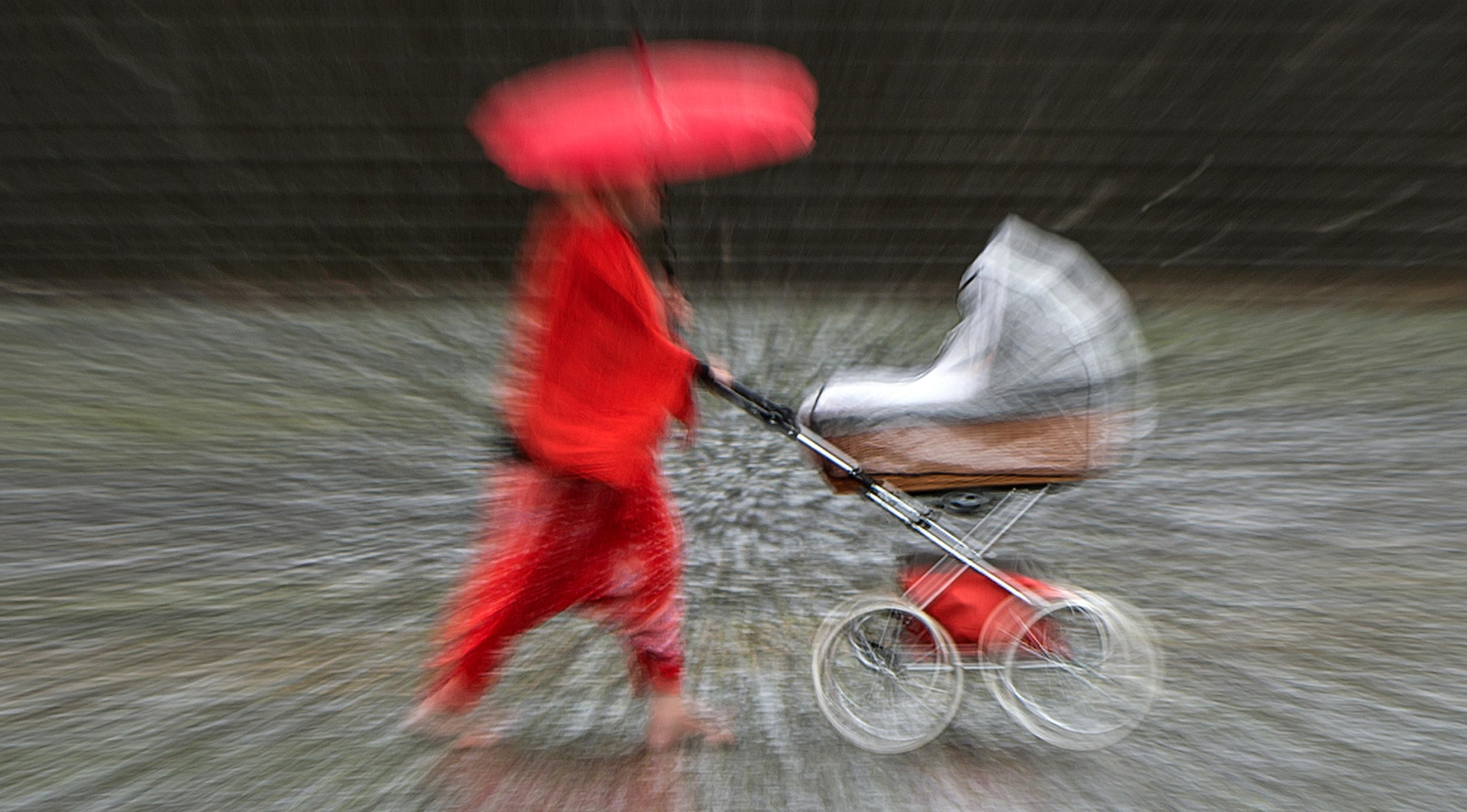 Seorang wanita berjalan selama hujan deras di Erfurt, Jerman, (29/6). Prakiraan cuaca memprediksi dalam beberapa hari Jerman dilanda hujan deras yang mengakibatkan banjir di beberapa titik ibu kota. (AP Photo / Jens Meyer)