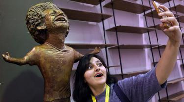Seorang peserta World Youth Forum berswafoto dengan patung bintang Liverpool, Mohamed Salah yang mulai dipamerkan di Sharm al-Sheikh, Mesir, Senin (5/11). Namun, bukannya menarik pujian, patung Mo Salah tersebut malah mendapat ejekan. (AP/Ayman Aref)