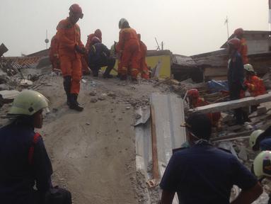 Sejumlah warga menyaksikan evakuasi korban rumah roboh di  Jalan Pulo, Tanah Tinggi, Johar Baru, Jakarta Pusa, Jumat (26/4). Enam orang masih terjebak dan tengah dalam proses evakuasi. (merdeka.com/Imam Buhori)