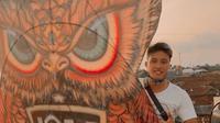 Bek Bali United, I Made Andhika Wijaya, berfoto dengan layangan raksasa yang diterbangkannya. (Bola.com/Iwan Setiawan)