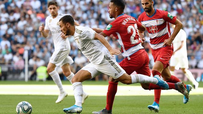 Gelandang Real Madrid, Eden Hazard, berusaha mengamankan bola saat melawan Granada pada laga La Liga Spanyol di Stadion Santiago Bernabeu, Madrid, Sabtu (5/10). Madrid menang 4-2 atas Granada. (AFP/Pierre-Philippe Marcou)