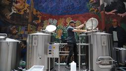 Pekerja mengecek proses pembuatan bir yang botolnya bergambar Presiden AS Donald Trump di perusahaan Cru Cru Brewery di Mexico City (15/6). Meski kontroversial penjualan bir ini sangat cepat laku di tempat tersebut. (AFP Photo/Bernardo Montoya)